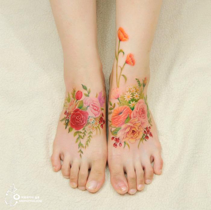 Tatuaje de acuarela en forma de flores colocado en los empeines del pie