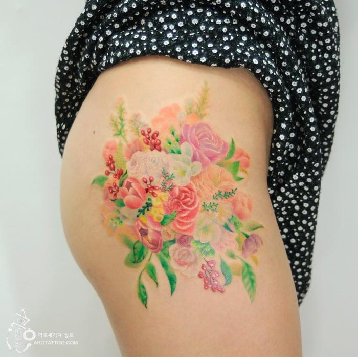 Tatuaje de acuarela en forma de ramo de flores colocado en el muslo