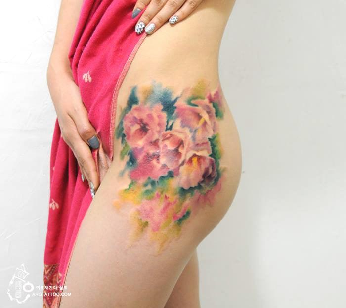 Tatuaje de acuarela en forma de tres flores colocado en la pierna