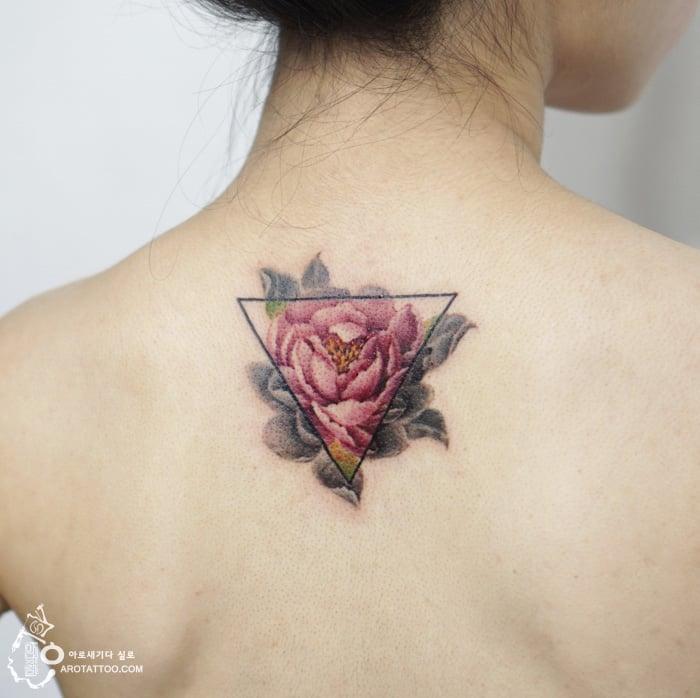 Tatuaje de acuarela en forma de rosa con un triangulo colocado en la espalda