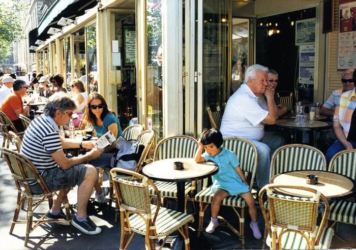 Kotori Kawashima fotografiando a una niña mientras está sentada en un café