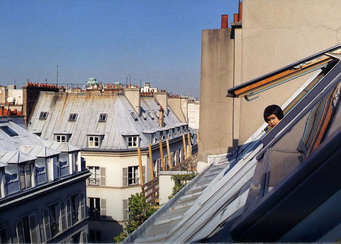 Kotori Kawashima fotografiando a una niña mientras se asoma por la ventana de un edificio