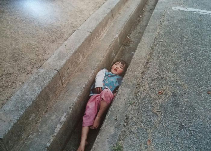 Kotori Kawashima fotografiando a una niña mientras está atorada entre la acera y la calle