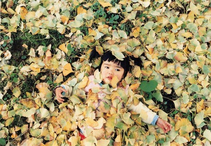 Kotori Kawashima fotografiando a una niña entre las hojas de un árbol