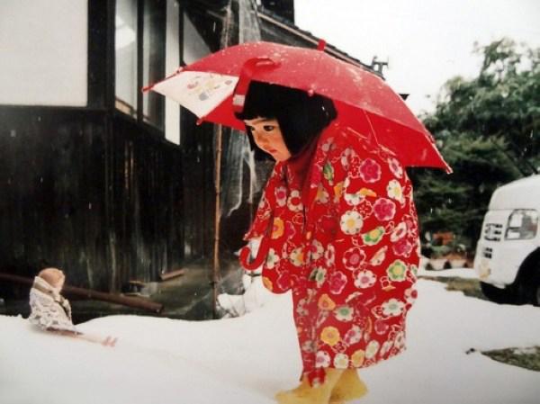 Kotori Kawashima fotografiando a una niña mientras está sujetando un paraguas