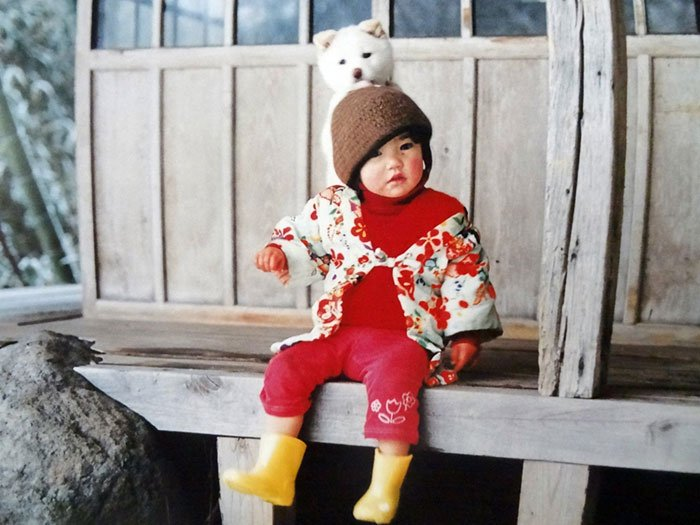 Kotori Kawashima fotografiando a una niña mientras está sentada junto a un perro