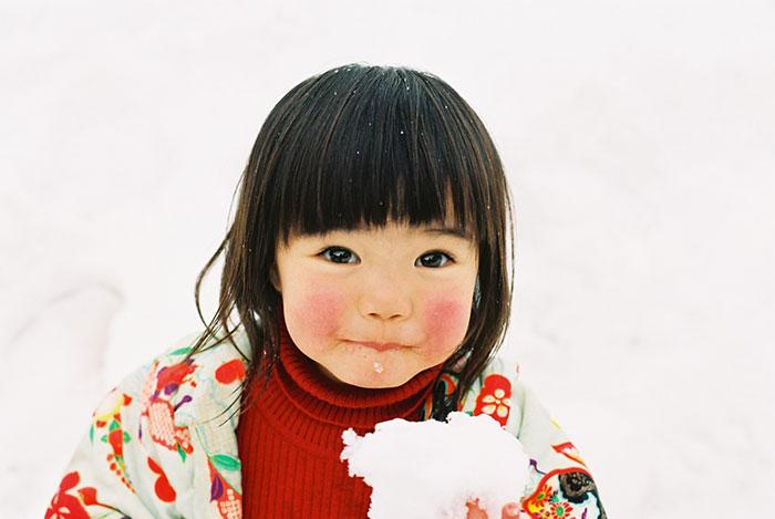 Kotori Kawashima fotografiando a una niña mientras tiene un copo de nieve en sus manos