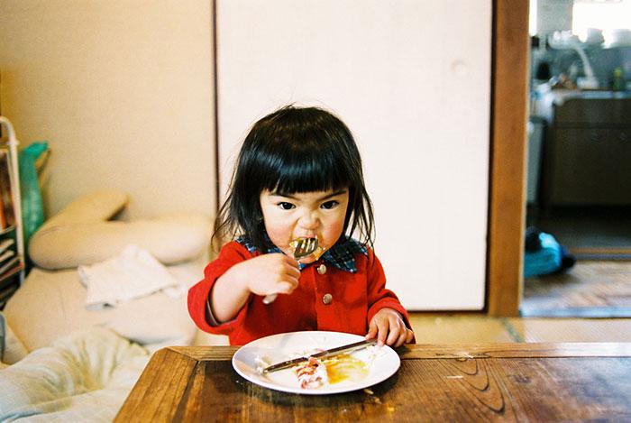 Kotori Kawashima fotografiando a una niña mientras está comiendo