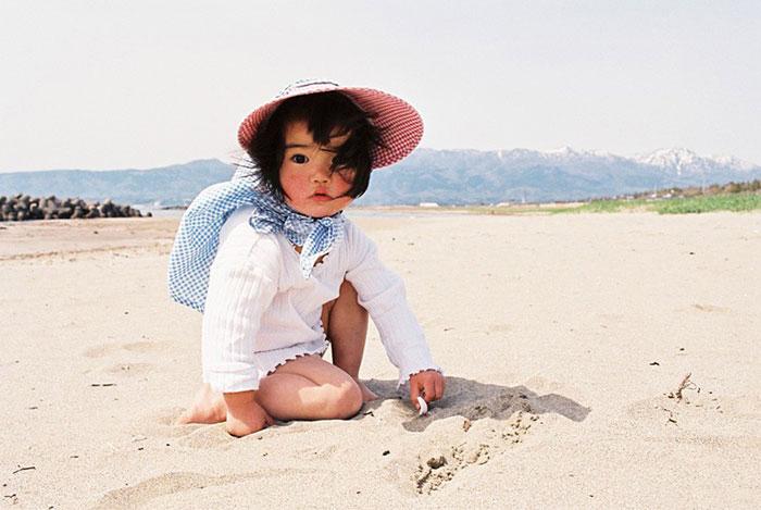 Kotori Kawashima fotografiando a una niña mientras está en la playa