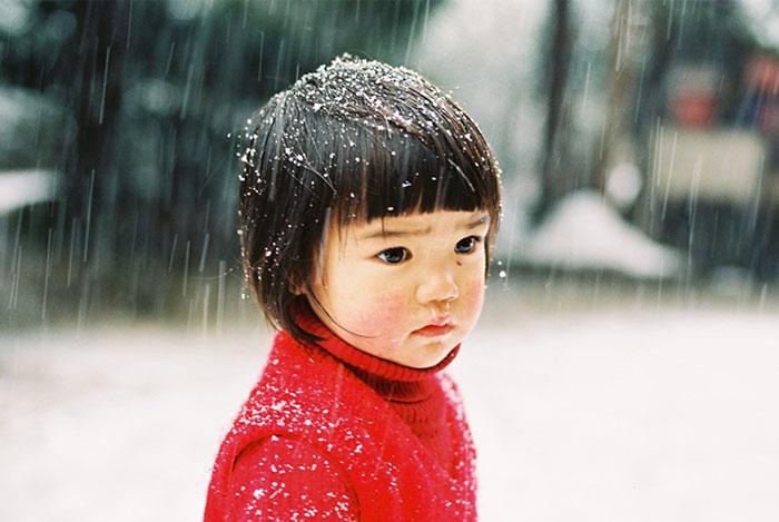 Kotori Kawashima fotografiando a una niña mientras está viendo la nieve caer
