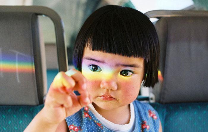Kotori Kawashima fotografiando a una niña mientras un arco iris se refleja en su cara