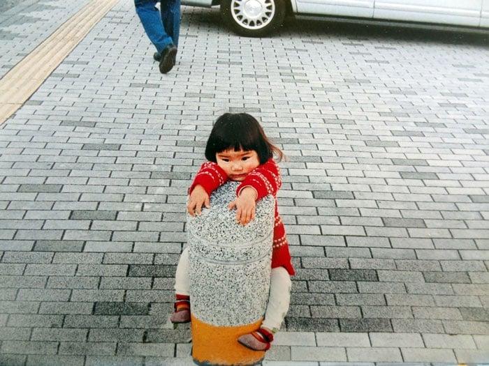 Kotori Kawashima fotografiando a una niña mientras ella se sujeta de un poste