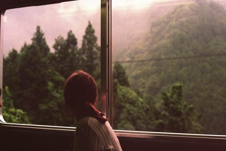 Chica viajando en bus viendo por la ventana