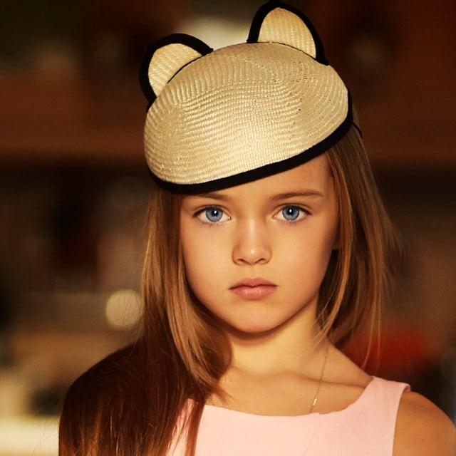 Kristina Pimenova la niña más bonita del mundo posando para una sesión de fotografías usando un sombrero color café y un vestido rosa