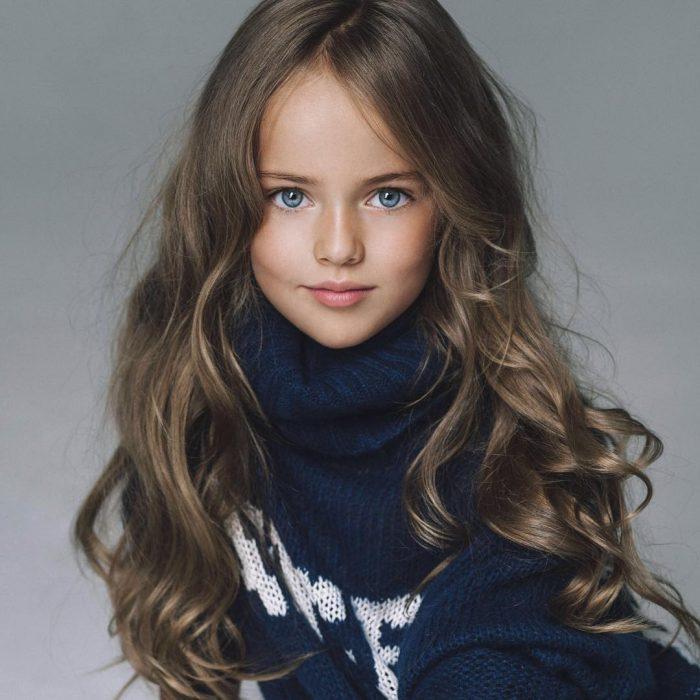 Kristina Pimenova la niña más bonita del mundo posando para una sesión de fotografías usando un suéter de color azul