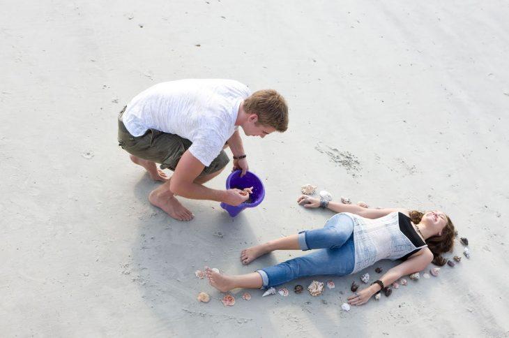 chica en la arena hombre la rodea con conchas enamorados