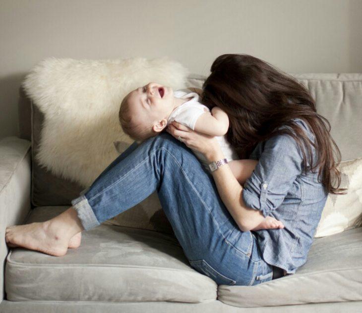 Chica sentada en un sofá haciéndole cosquillas a un bebé