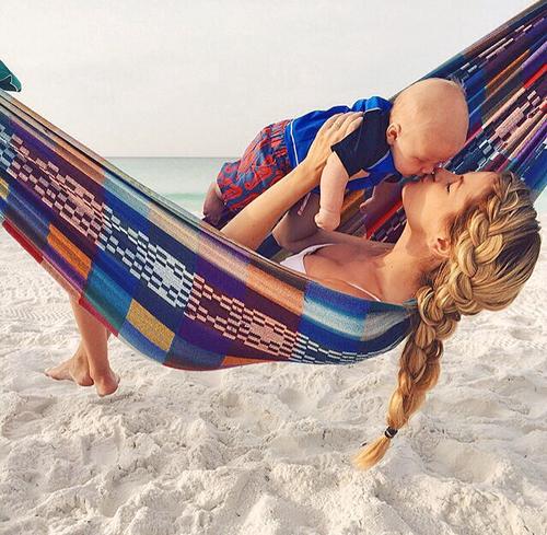 Chica en una hamaca besando a su bebé mientras lo sostiene en brazos