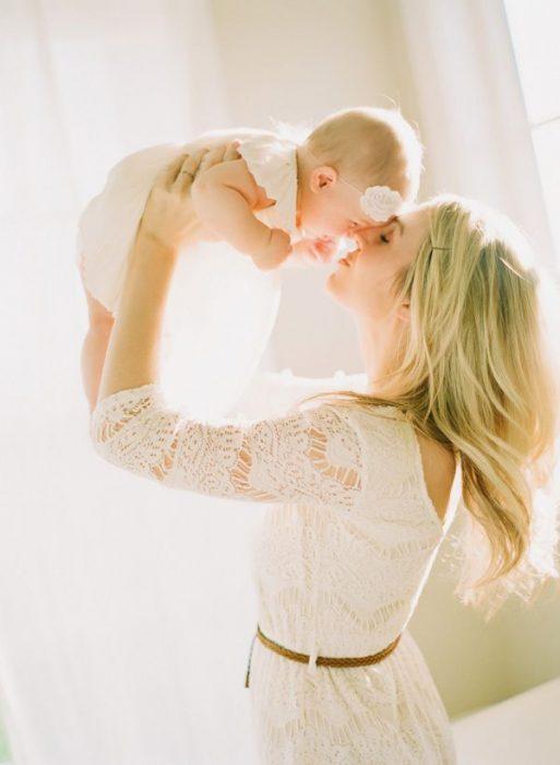 Chica cargando a su bebé en brazos y besándolo