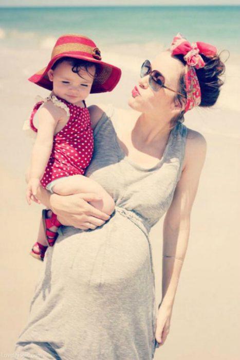 Chica embarazada cargando a su bebé en brazos