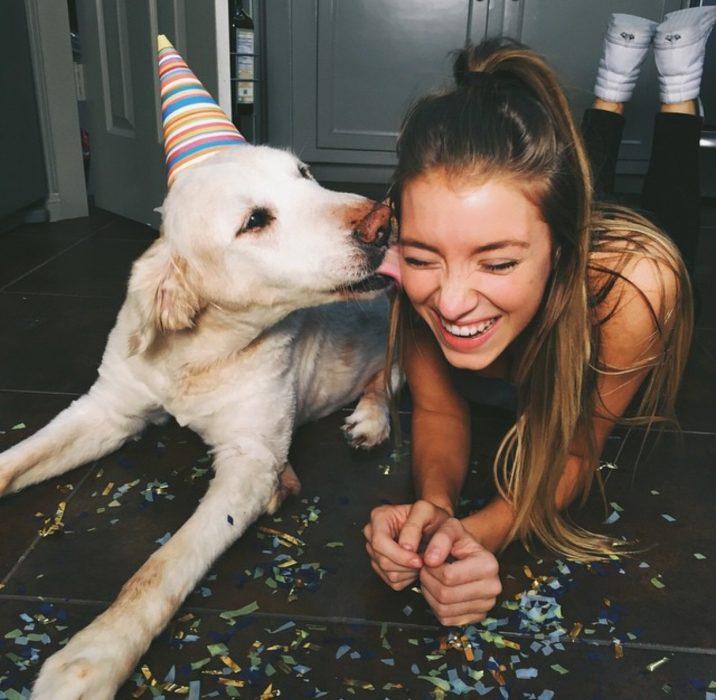Chica sentada junto a un perro mientras la lame en la mejilla