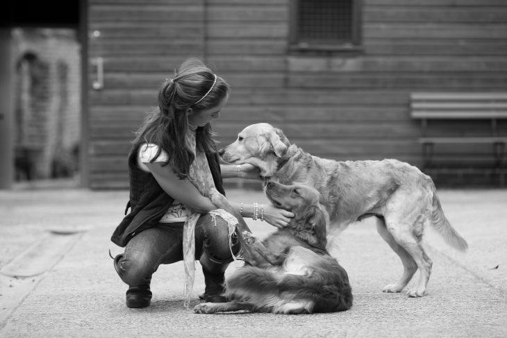 Chica sentada en el suelo acariciando a dos perros