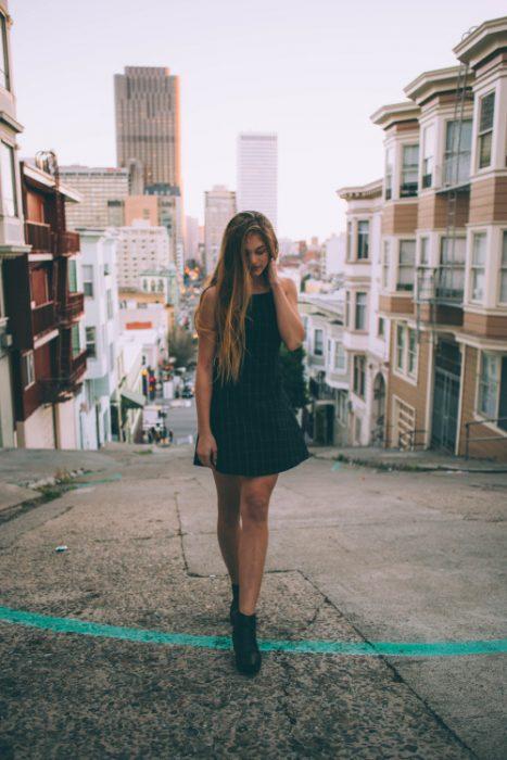 Chica con vestido negro caminando en la calle
