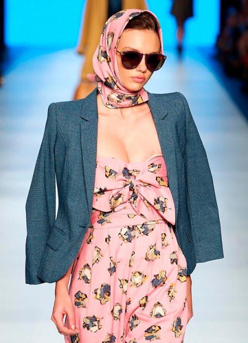 Chica caminando por una pasarela mientras está usando un pañuelo rosa en la cabeza