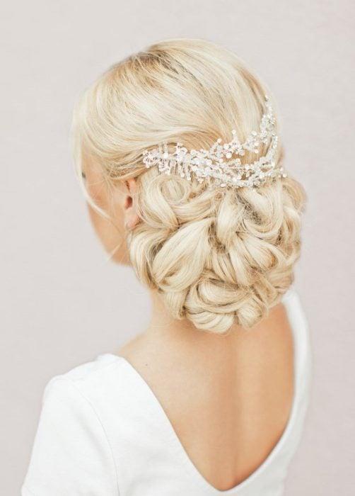 peinados para el día de tu boda. chica usando un chongo bajo con chinos y accesorios de ctistal