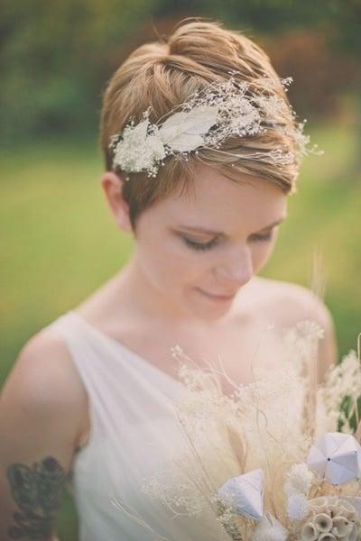 peinados para el día de tu boda. chica usando una diadema de flores blancas en su cabello corto