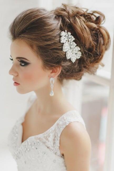 Peinados para el día de tu boda chica con un chongo despeinado y una hoja brillante como accesorio