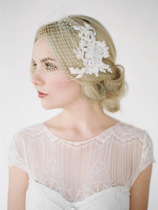 Peinados para el día de tu boda, chica usando un peinado recogido bajo con un velo