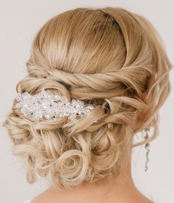 Peinados para el día de tu boda, chica usando unpeinado bajo con un adorno de cristal en medio