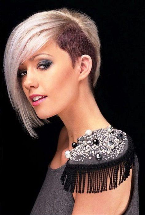 Chica con el cabello en corte bob rapado de un lado y pintado en color rosa con lila