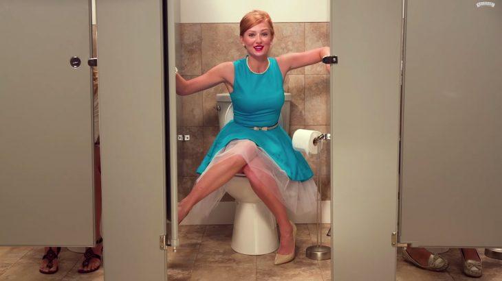Mujer sentada sobre la taza de baño