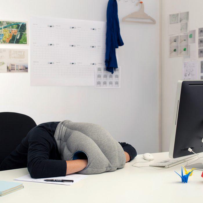 Chica durmiendo en la oficina dentro de una almohada