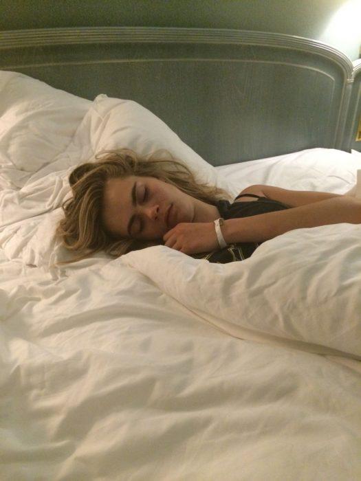 Cara Delevinge durmiendo sobre una cama blanca