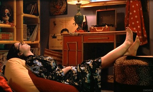 Chica recostada en un sofá con los pies sobre un escritorio