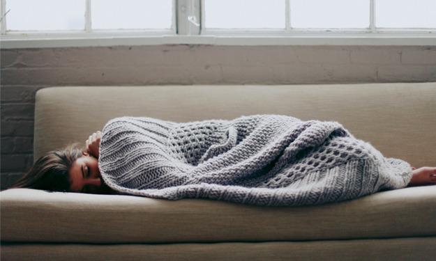 Chica recostada sobre un sofá tapada con una manta de estambre