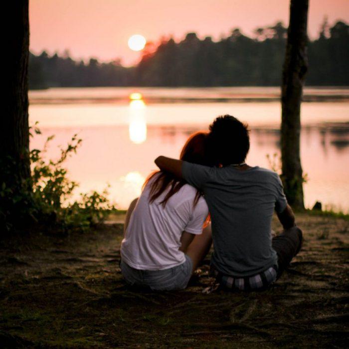 pareja sentados frente a un lago