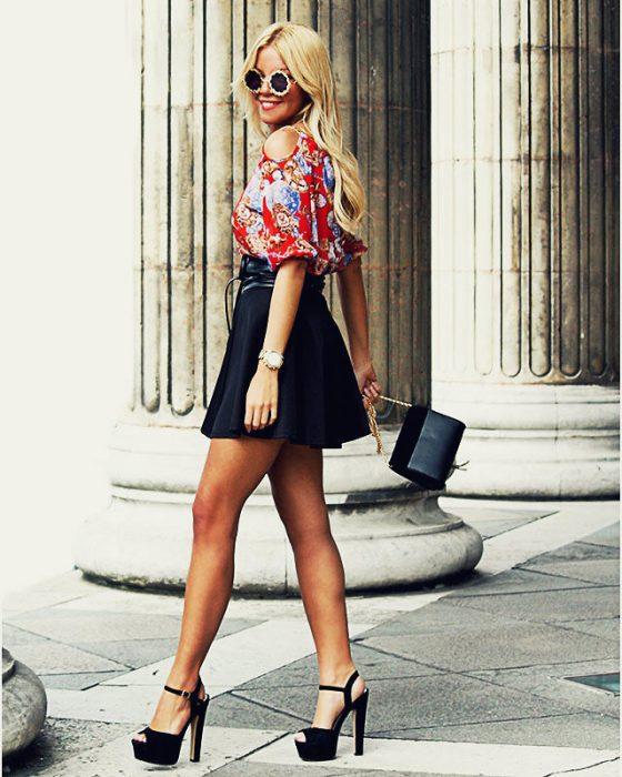 Chica alta en tacones caminando por la calle