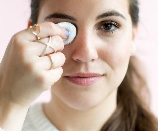 Chica sosteniendo un algodón con removedor de maquillaje sobre su ojo