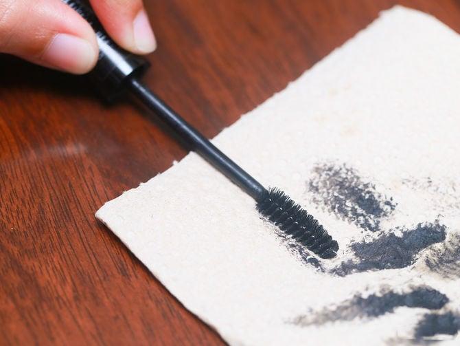 Chica elimando el exceso de rímel en una toalla de papel