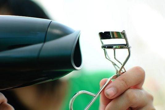 Chica calentando el rizador de pestañas con un secador de cabello