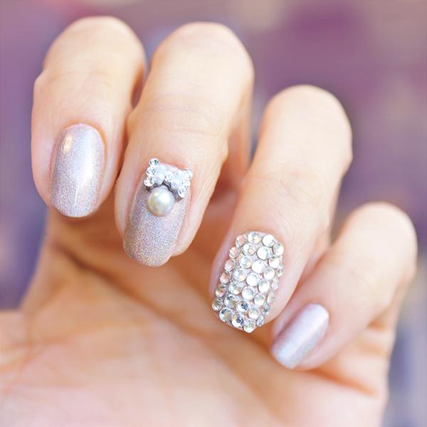 Uñas de novia en color lila con brillos y un moño en color plata