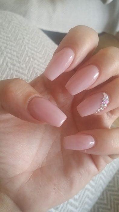 Uñas de una chica pintadas en tono nude con piedras