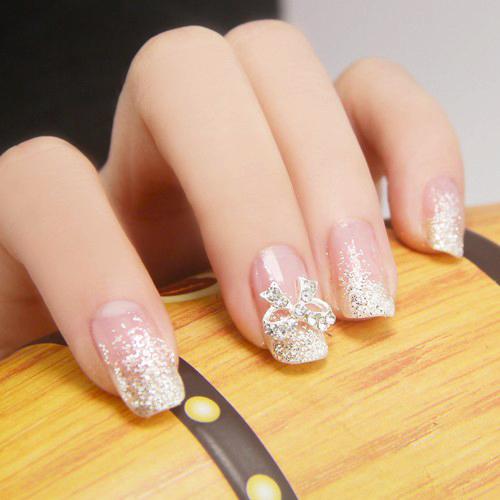 Uñas de una novia al natural con brillos dorados y un moño