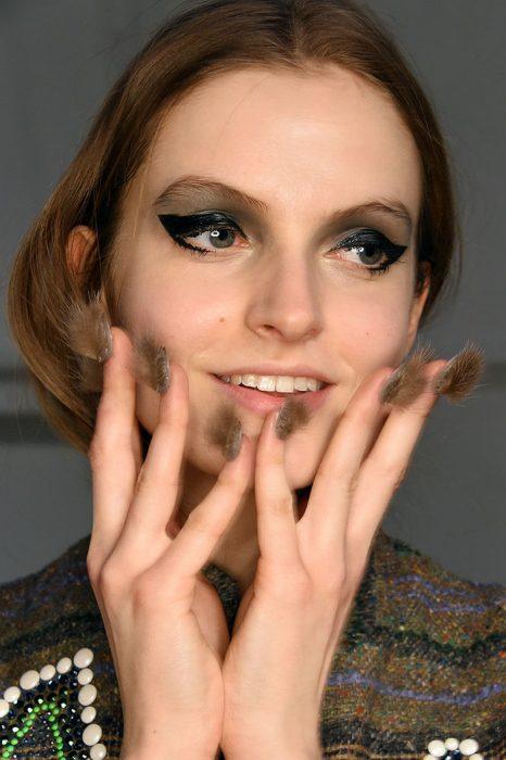 Modelo con un estilo de uñas peludas en color café con gris