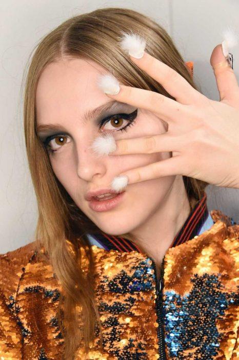 Modelo con un modelo de uñas peludas en color blanco