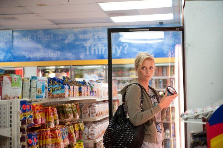 mujer rubia de pie en refrigerador de super mercado